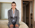 Happy business woman sitting on bed in hotel room modern Royalty Free Stock Photography