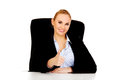 Happy business woman sitting behind the desk and shows thumb up Royalty Free Stock Photo