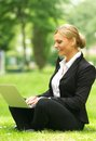Happy business woman sitting on grass with laptop portrait of a Stock Image