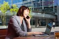 Happy business woman talking on mobile phone while working on laptop Royalty Free Stock Photo