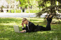 Happy business woman using laptop in a city park blond Royalty Free Stock Photo