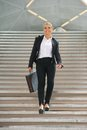 Happy business woman walking downstairs with briefcase portrait of a Royalty Free Stock Photo