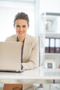 Happy business woman working on laptop in office modern Stock Photos