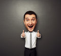 Happy businessman with big head laughing showing two thumbs up and funny picture over dark background Stock Photo