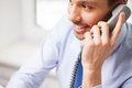 Happy businessman calling on phone at office