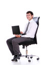 Happy businessman on chair with laptop Royalty Free Stock Photo