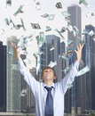 Happy businessman and flying dollar banknotes against skyscrapers Royalty Free Stock Photos
