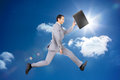 Happy businessman jumping with his briefcase in bright blue sky background Royalty Free Stock Image