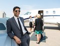 Happy businessman leaning on car at airport with airhostess and pilot greeting business people against private jet Stock Photography