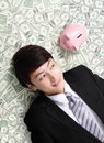 Happy businessman look pink piggy bank and lying on money bed asian man Royalty Free Stock Photography