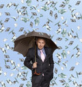 Happy businessman man with umbrella and flying dollar banknotes against blue sky Royalty Free Stock Photos
