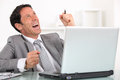 Happy businessman sat at his desk Stock Photo