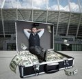 Happy businessman sits in the case full of dollars Royalty Free Stock Photo