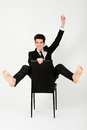 Happy businessman sitting in a chair with raised arm Stock Images
