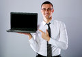 Happy businessman standing with laptop