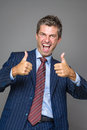 Happy businessman in thumbs up gesture Stock Images