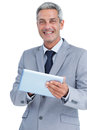 Happy businessman using tablet pc looking at camera on white background Stock Photo