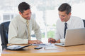 Happy businessmen working together and smiling in the office Royalty Free Stock Image