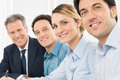 Happy businesspeople in a row portrait of smiling looking at camera sitting Royalty Free Stock Image