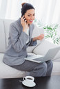 Happy businesswoman calling with her mobile phone and using laptop sitting on sofa Royalty Free Stock Photo