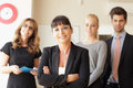 Happy businesswoman with colleagues in the background at office Royalty Free Stock Image