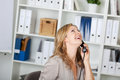 Happy businesswoman communicating on phone portrait of land line at office Royalty Free Stock Photography