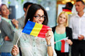 Happy businesswoman holding flag of romania in front colleagues Royalty Free Stock Image