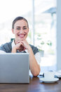 Happy businesswoman looking at camera behind laptop computer in office Royalty Free Stock Photo