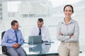 Happy businesswoman posing leaning against the desk Royalty Free Stock Photo