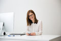 Happy businesswoman sitting at her workplace in office Royalty Free Stock Photo