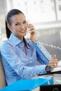 Happy businesswoman speaking on phone landline smiling at camera Stock Photo