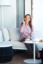 Happy businesswoman talking on the phone in a coffee shop and writing organizer Royalty Free Stock Images