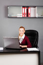 Happy businesswoman typing on laptop at her desk looking camera in bright office Royalty Free Stock Photography