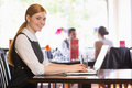 Happy businesswoman typing on laptop while smiling at camera in a restaurant Stock Photography