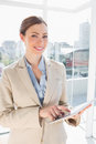 Happy businesswoman using her tablet pc and looking at camera Stock Photos