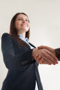 Happy businesswoman wearing suit shaking male hand, focus on han Royalty Free Stock Photo