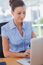 Happy businesswoman working on her laptop and smiling in the office Royalty Free Stock Images