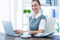 Happy businesswoman working on laptop computer and looking at camera in office Stock Images