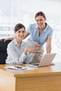 Happy businesswomen at desk smiling at camera camea with laptop in office Royalty Free Stock Images