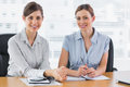 Happy businesswomen working together and smiling at camera desk in office Royalty Free Stock Photo