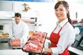 Happy butcher holding meat tray in store portrait of female with colleague working background Royalty Free Stock Images