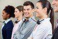 Happy call center employee standing in row with portrait of male colleagues at office Royalty Free Stock Photography