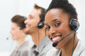 Happy call center operator closeup of african american telephone with her colleagues Stock Image
