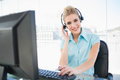 Happy call centre agent working on computer in bright office Royalty Free Stock Images
