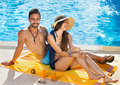 Happy carefree couple relaxing poolside beautiful young in their swimsuits enjoying the hot summer sun on a tropical vacation Stock Photo