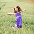 Happy carefree girl in a cornfield young teenage jumping for joy with her arms outstretched as she enjoys the summer Royalty Free Stock Photography