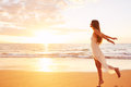 Happy carefree woman dancing on the beach at sunset free lifestyle concept Royalty Free Stock Images
