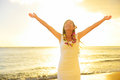 Happy carefree woman free in hawaii beach sunset beautiful the golden sunshine glow of with arms outspread and Royalty Free Stock Image