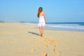 Happy carefree woman walking on beach celebrating her freedom summer woman background of the ocean and sand back view of girl Stock Image