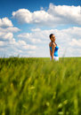Happy carefree young woman in a green wheat field smiling as she trails her hand through the plants low angle distance view Stock Photo